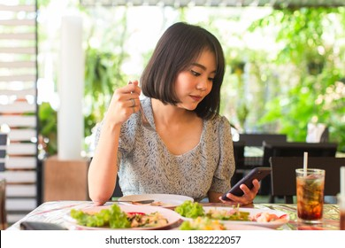 young asian woman holding smartphone with many food on the table