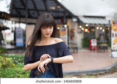 Young asian woman holding smartphone and looking at wristwatch with worry face, waiting for someone