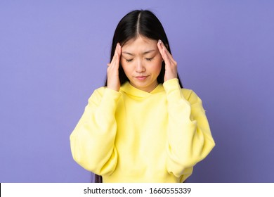 Young asian woman isolated on purple background with headache
