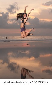 Young asian woman jumping in the air on beach at sunset