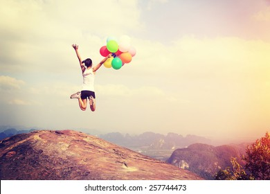young asian woman jumping on mountain peak cliff edge with colored balloons