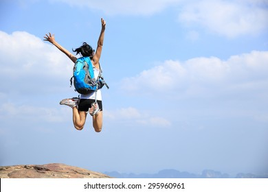 young asian woman jumping on mountain peak cliff