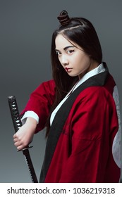 young asian woman in kimono holding katana and looking at camera isolated on grey