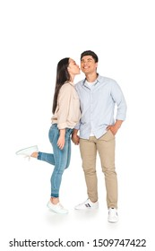 young asian woman kissing happy boyfriend on white background