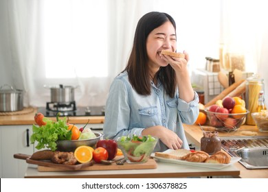 Young Asian woman in the kitchen prepare and eating sandwich for breakfast