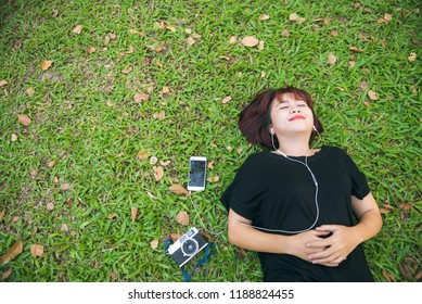 Young Asian woman laying on the green grass listening to music in the park with a chill emotion. Young woman relaxing on the grass with her music playlist. Outdoor activity in the park concept.