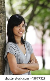 A young Asian woman leaning against a tree