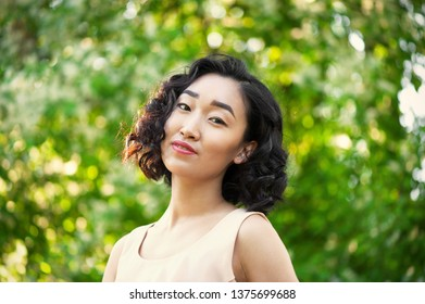 Young asian woman in light dress at sunny park