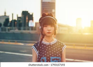 Junge asiatische Frau hört Musik-Outdoor-Kamera - Diverse freundliche Frau, die sich mit der Kamera herumstarrt und Musik genießt - emotionales, freundliches, einfühlsames Konzept