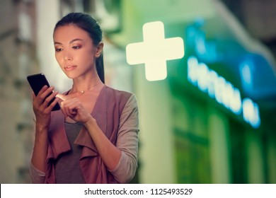 A young asian woman is locating a pharmacy store at night with her smart phone mobile device. Communicate about open pharmacies at night, using navigation to locate stores, maps, health, on call