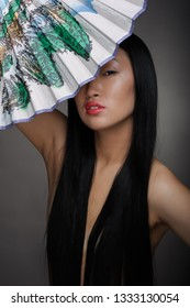 Young asian woman with long hair and fan