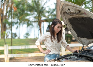 Young Asian woman looking at her broken down car