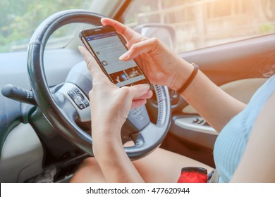 Young asian woman looking to her smartphone while driving car - rear view, sun shines through front window