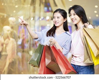 young asian woman looking into shop windows in shopping mall