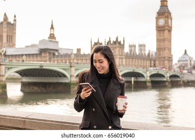 Young Asian woman looking at smart phone outdoor in late winter near Westminster Bridge, London, England. Asian business women with smartphone and holding coffee near Big Ben.