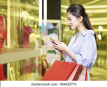 young asian woman looking using cellphone while shopping in mall or department store