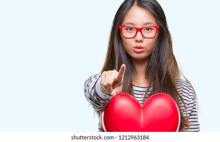 Young asian woman in love holding read heart over isolated background pointing with finger to the camera and to you, hand sign, positive and confident gesture from the front