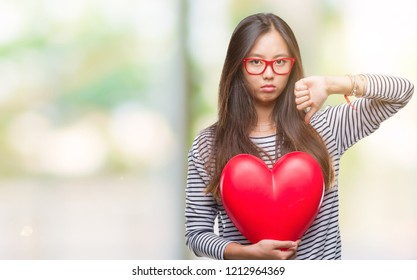 Young asian woman in love holding read heart over isolated background with angry face, negative sign showing dislike with thumbs down, rejection concept