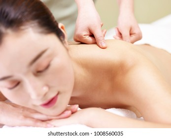 young asian woman lying on front on bed receiving massage in spa salon.