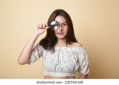 Young Asian woman with a magnifying glass on beige background