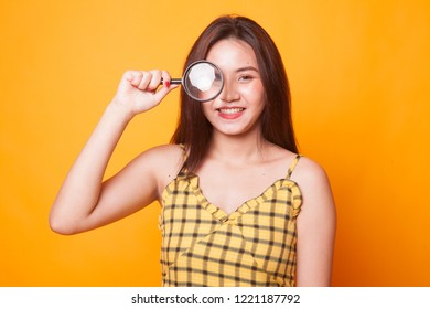 Young Asian woman with a magnifying glass on yellow background