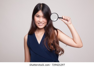 Young Asian woman with a magnifying glass on gray background