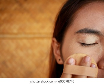 Young Asian woman make up yourself, Applying powder for perfact make-up by powder puff, Image close-up
