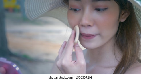 Young Asian woman makeup applying foundation on her face using sponge, cosmetic beauty concept, close up.