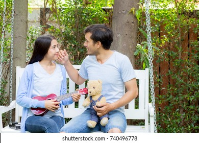 Young asian woman and man couple sitting at park playing ukulele and sing a song outdoors relax concept.