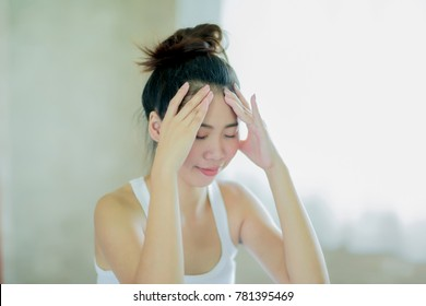 Young asian woman massaging her head for relieve headache