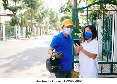 Young Asian woman in medical mask receiving order and leaving tips for the courier via application on smartphone