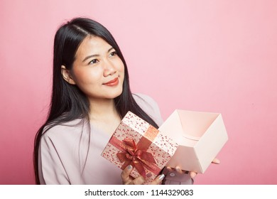 Young Asian woman open a gift box on pink background