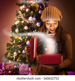 Young Asian woman opening a present full of Christmas magic.