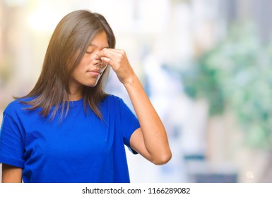Young asian woman over isolated background tired rubbing nose and eyes feeling fatigue and headache. Stress and frustration concept.