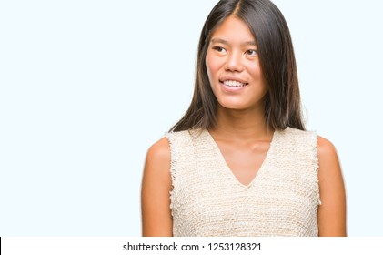 Young asian woman over isolated background looking away to side with smile on face, natural expression. Laughing confident.