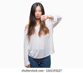 Young asian woman over isolated background looking unhappy and angry showing rejection and negative with thumbs down gesture. Bad expression.