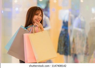 Young asian woman with packages, purchases, discounts.