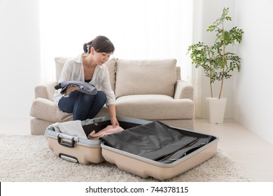 young asian woman packing suitcase in living room
