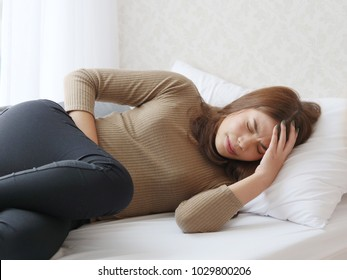 young Asian woman in pain with Period cramps in living room
