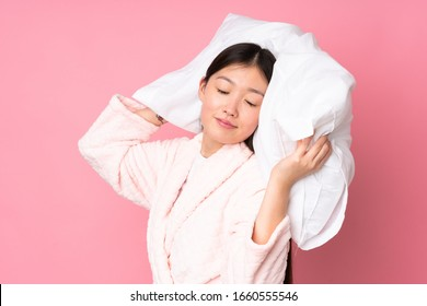 Young Asian woman in pajamas isolated on pink background