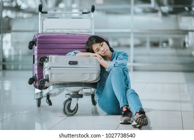 Young Asian woman passenger sleeping with luggage trolley at an airport terminal waitng for departure flight