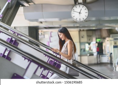 Young Asian woman passenger using smart mobile phone and walking up the stairs in subway station when traveling in big city,japanese,chinese,Korean lifestyle and daily life,commuter and transportation