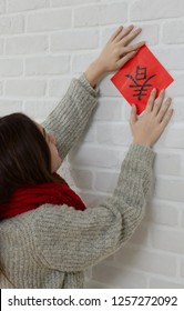 """Young asian woman pastes spring couplet. It is the tradition of Chinese culture to stick spring couplet to the doors for Chinese New Year. The word on the spring couplet means """"spring"""""""