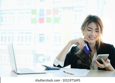 Young asian woman paying with credit card on smart phone at home office, Online payment concept.