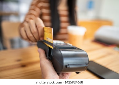 Young asian woman paying her order by credit card on payment terminal in coffee shop.