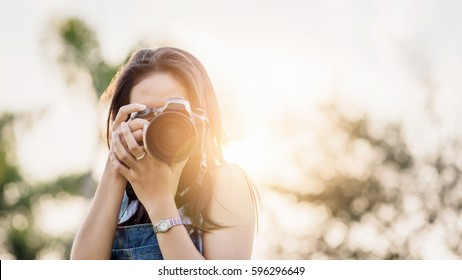 Young Asian woman photographer.