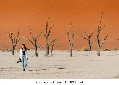 Young Asian woman photographer and traveler walking on clay pan near dead trees in deadvlei (Sossusvlei), famous natural landmark in Namib desert of Namibia, Africa