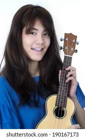 Young Asian woman playing ukulele isolated on white background.