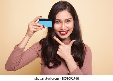 Young Asian woman point to a blank card on beige background