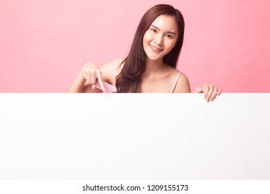 Young Asian woman point to a  blank sign on pink background